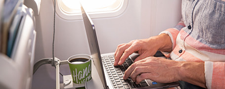 A passenger using the wifi on an Alaska Airlines flight with their laptop.